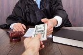 stock photo of take responsibility  - Midsection of judge taking bribe from client at desk in courtroom - JPG