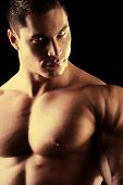 Close-up shot of a handsome muscular bodybuilder posing over black background.