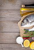 Fresh dorado fish cooking with spices and condiments on wooden table with copy space