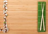 Chopsticks and sakura branch over bamboo mat on table with copy space