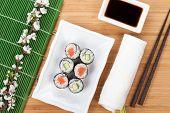 Sushi maki set with fresh sakura branch over bamboo table