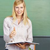 Smiling female teacher in school holding her thumbs up