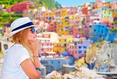 Traveler girl enjoying colorful cityscape, spending summer vacation in Europe, Italy, Cinque Terre,