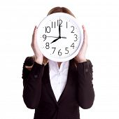 Business woman wearing formal suit and holding big clock on face, isolated on white background, punctual worker concept