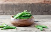 wooden bowl full  of green peas pods
