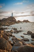 La Corbiere Lighthouse at sunset on Jersey in the Channel Islands, in the English Channel.