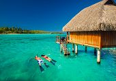 foto of beach hut  - Young couple snorkeling from hut over blue tropical lagoon - JPG