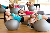 fitness, sport, training and lifestyle concept - group of smiling women with exercise balls in gym