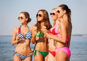 summer vacation, holidays, food, travel and people concept - group of smiling young women eating ice