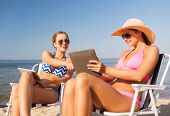 summer vacation, travel, technology and people concept - smiling women with tablet pc computers sunb