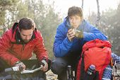 Male hiker reading map while friend having coffee in forest
