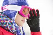 Side view close-up of beautiful young woman in ski goggles looking away