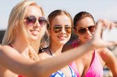 summer vacation, holidays, travel, technology and people concept- group of smiling young women on be