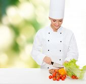cooking and food concept - smiling female chef chopping vegetables