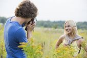 Young man photographing girlfriend in field