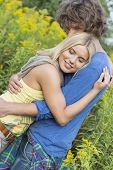 Side view of romantic couple hugging in field