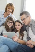Family using digital tablet together in living room
