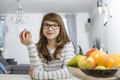 Portrait of teenage girl holding apple at home