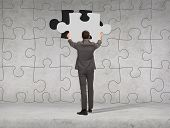 business, development and people concept - businessman in suit setting piece of puzzle to the wall b