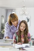 Mother guiding daughter in doing homework at table
