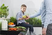 Midsection of father giving pear to son in kitchen