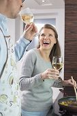 Cheerful couple having wine while cooking in kitchen