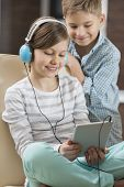 Cute girl listening music on digital tablet while brother standing behind her at home
