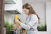 Smiling woman preparing spaghetti in kitchen