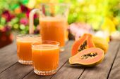 stock photo of fruit-juice  - Two glasses of freshly prepared papaya juice with pitcher and papaya fruits in the back on table outdoors  - JPG