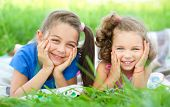 Two little girls are laying on green grass supporting their heads with hands, outdoor shoot