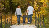 Happy Young Family In Autumn Making A Walking Tour.