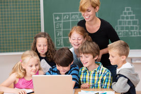 stock photo of cluster  - Group of small children ion class with a teacher clustered around a laptop computer laughing and smiling as an attractive woman keeps an eye on them - JPG