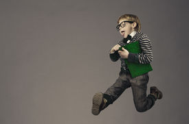 stock photo of schoolboys  - child running back to school funny kid portrait jumping smart schoolboy with glasses and book - JPG