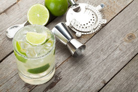 stock photo of cold drink  - Classic margarita cocktail with salty rim on wooden table with limes and drink utensils - JPG