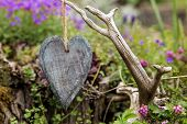 Hanging Wooden Heart In Front Of A Romantc Garden