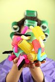 Girl in hair curlers on colorful background