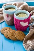 pic of blanket snow  - Two blue cup of tea in knitted sweater with hearts felt standing next to tangle bright filaments and blanket knitted on blue background - JPG