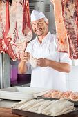 Portrait of happy mature butcher holding chicken meat in butchery