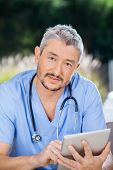 stock photo of nurse  - Portrait of male nurse using digital tablet at nursing home - JPG