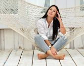 Beautiful Smiling Young Woman Relaxing In Hammock At Home