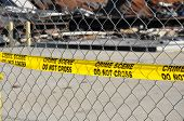 stock photo of crime scene  - A bright yellow warning tape that reads Crime Scene Do Not Cross on a chain link fence - JPG