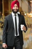 stock photo of turban  - Young indian businessman in turban with coffee. ** Note: Soft Focus at 100%, best at smaller sizes - JPG