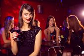 Pretty brunette drinking a cocktail at the nightclub
