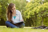 Smiling student sitting and reading book in park at school