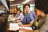 Student looking at camera while studying with classmates in library