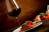 Bruschetta Appetizer With Red Wine On Wooden Table