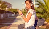 Young girl with skateboard and headphones listening music outdoors