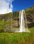 Seljalandsfoss waterfall in Iceland. Summer sunny day. Large rainbow decorates a drop of water
