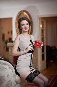 Happy smiling attractive woman wearing an elegant dress and black stockings sitting on the sofa
