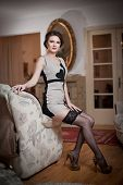 pic of tight dress  - Happy smiling attractive woman wearing an elegant dress and black stockings sitting on the sofa arm - JPG